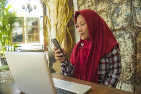 Muslim student girl in hijab networking with laptop . Young happy and beautiful Asian Indonesian woman in Islam head scarf working at cafe using computer and mobile phone