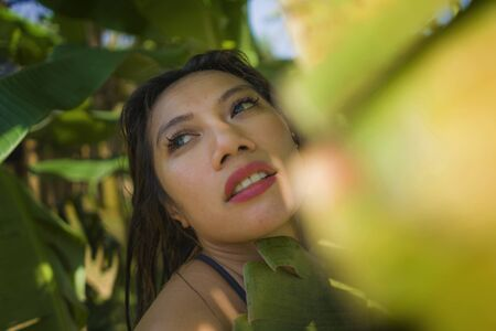 young beautiful and happy Asian Indonesian woman in bikini posing between leaves of banana tree smiling natural isolated on exotic tropical background in Summer holiday travel and beauty concept