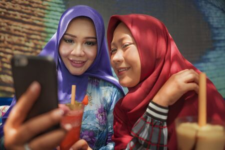 Muslim woman and her teenager daughter . Happy Asian Indonesian girl taking selfie with her beautiful mum both in traditional Islamic hijab head scarf having fun together at cafe Stock Photo