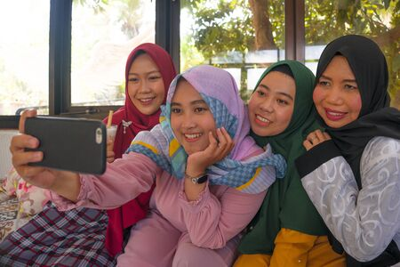 Muslim woman and her teenager daughters . Happy Asian Indonesian sisters taking selfie with her mum wearing traditional Islamic hijab head scarf having fun together on holidays Foto de archivo