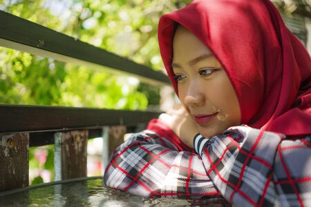 lifestyle portrait of young beautiful and relaxed Asian Indonesian Muslim girl sitting outdoors wearing traditional islamic hijab head scarf thinking and daydreaming happy