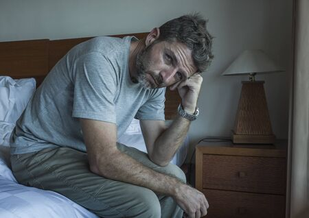 Attractive depressed and upset man thoughtful at home bedroom . dramatic lifestyle portrait of handsome guy sitting on bed feeling sad thinking and suffering depression and anxiety problem