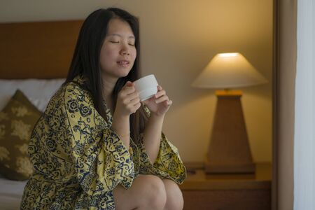 morning lifestyle portrait of young beautiful and natural Asian Korean woman drinking coffee in bed after wake up smiling happy and cheerful enjoying the view relaxed in stylish kimono bathrobe Banque d'images - 129522502