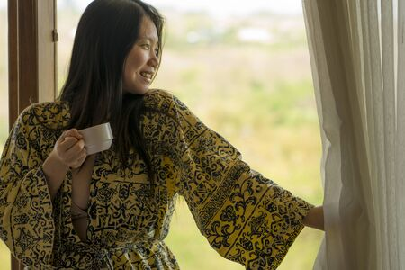 morning lifestyle portrait of young beautiful and natural Asian Chinese woman drinking coffee in bed after wake up smiling happy and cheerful enjoying the view relaxed in stylish kimono bathrobe Banque d'images - 129522508