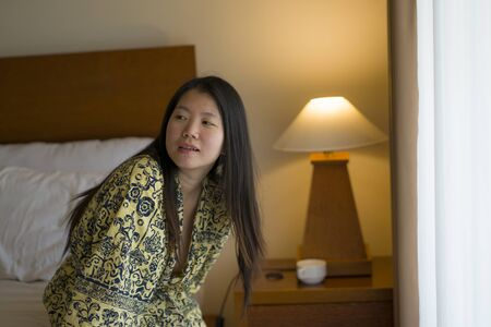 morning lifestyle portrait of young beautiful and natural Asian Korean woman drinking coffee in bed after wake up smiling happy and cheerful enjoying the view relaxed in stylish kimono bathrobe Banque d'images - 129522509