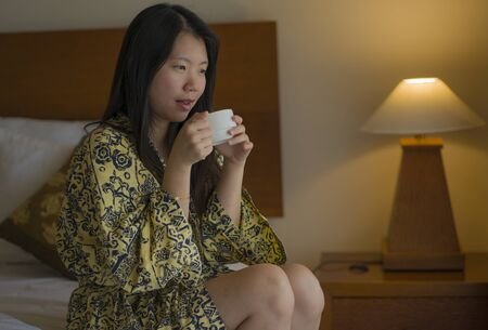 morning lifestyle portrait of young beautiful and natural Asian Chinese woman drinking coffee in bed after wake up smiling happy and cheerful enjoying the view relaxed in stylish kimono bathrobe Banque d'images - 129522505