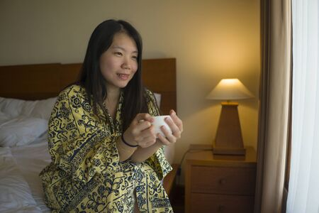 morning lifestyle portrait of young beautiful and natural Asian Chinese woman drinking coffee in bed after wake up smiling happy and cheerful enjoying the view relaxed in stylish kimono bathrobe Banque d'images - 129522511