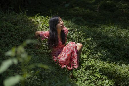 young beautiful and happy Asian Chinese woman in stylish dress enjoying adventure holiday trip exploring the beauty of nature at tropical island jungle lying on green environment relaxed