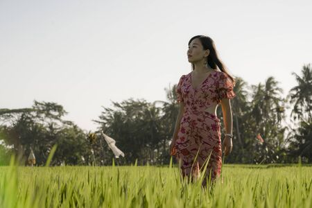 natural and fresh lifestyle portrait of  young beautiful and attractive Asian Chinese woman in elegant dress walking on green rice field enjoying exotic Summer holidays trip in nature
