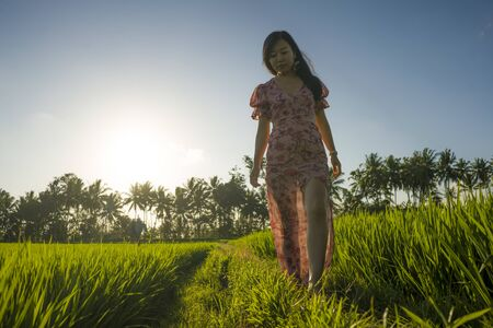 tropical sunset bliss. Young beautiful and attractive Asian Chinese woman in elegant dress walking on green rice field enjoying exotic Summer holidays trip in nature and tourist destination concept