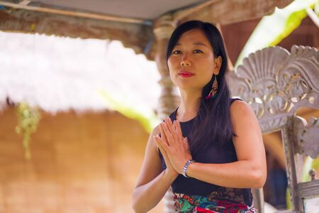 young natural and attractive Asian Chinese woman practicing yoga and meditation exercise sitting lotus pose outdoors at beautiful garden serene and calm in wellness and healthy lifestyle