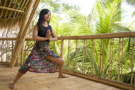 young natural and attractive Asian Chinese woman practicing yoga and meditation exercise outdoors at beautiful wooden joglo studio with tropical jungle view in wellness and healthy lifestyle