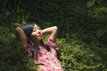 young beautiful and happy Asian Korean woman in stylish dress enjoying adventure holiday trip exploring the beauty of nature at tropical island jungle lying on green environment relaxed 写真素材