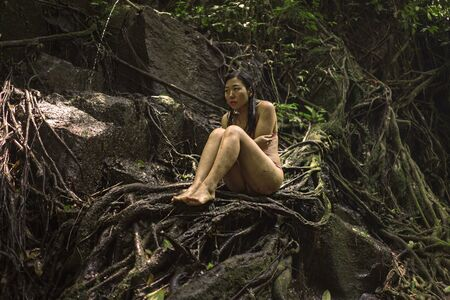 beautiful woman at tropical enchanted forest . Young attractive Asian Chinese girl in bikini sitting on tree trunk at tropical paradise jungle with a mysterious and magical feeling in wanderlust conce 写真素材