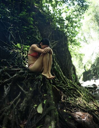 beautiful woman at tropical enchanted forest . Young attractive girl in bikini sitting vulnerable and mysterious on tree trunk at tropical paradise jungle with magical feeling in wanderlust concept