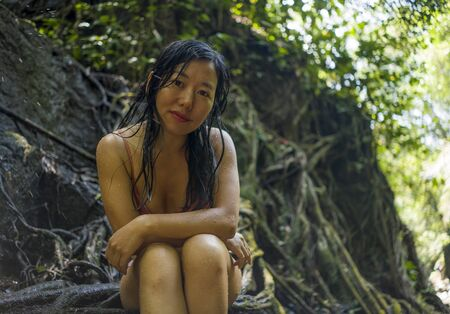 beautiful woman at tropical enchanted forest . Young attractive Asian Korean girl in bikini sitting on tree trunk at tropical paradise jungle with a mysterious and magical feeling in wanderlust concep 写真素材