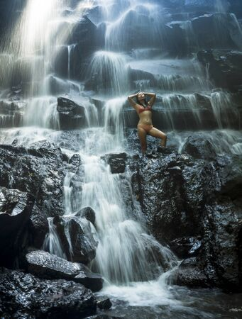 natural portrait of young beautiful and happy Asian Chinese woman in bikini enjoying nature at tropical paradise waterfall with magical feeling in travel destination and soul inspiration concept