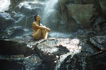 natural portrait of young beautiful and happy Asian Korean woman in bikini enjoying nature at tropical paradise waterfall with magical feeling in travel destination and soul inspiration concept 写真素材