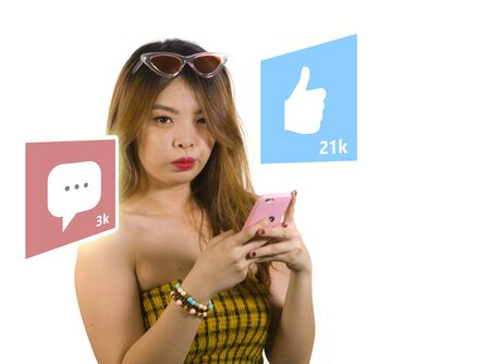 lifestyle portrait of young happy and attractive Asian Korean woman using internet mobile phone composite with social media app likes and chat comments icons in influencer success concept Stock Photo