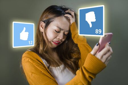 young cute and sad Asian Chinese girl feeling unhappy and desperate holding mobile phone looking more dislikes than likes on her internet social media post in cyber bullying and influencer obsession
