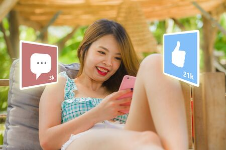 lifestyle portrait of young happy and attractive Asian Korean woman using internet mobile phone composite with social media app likes and chat comments icons in influencer success