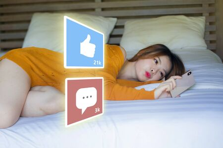 lifestyle portrait of young happy and attractive Asian Chinese woman using internet mobile phone composite with social media app likes and chat comments icons in influencer success Stock Photo