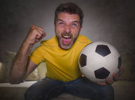 portrait at home of young happy and excited man watching European football game on TV celebrating goal on couch screaming spastic gesturing crazy cheerful as soccer fan enjoying victory