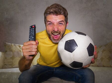 portrait at home of young happy and excited man watching European football game on TV celebrating goal on couch screaming spastic gesturing crazy cheerful as soccer fan enjoying victory 版權商用圖片 - 130731820