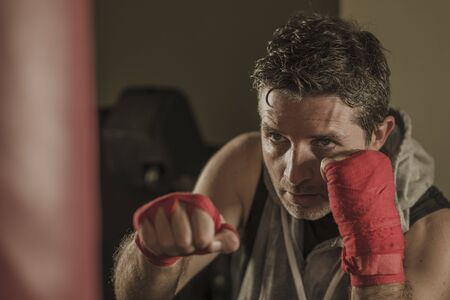 lifestyle gym portrait of young attractive and fierce looking man training boxing at fitness club doing heavy bag punching workout with hands and wrist wraps in badass fighter look