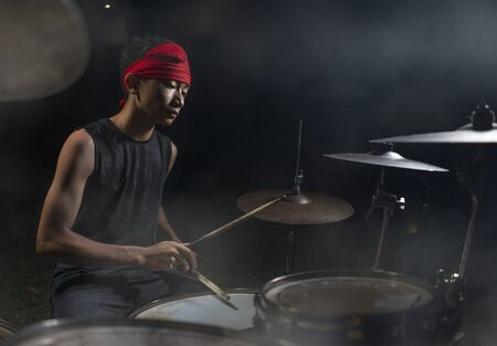 Teenager rock band drummer . cool and talented Asian American mixed ethnicity teenage boy playing drums in headband performing song in dark foggy stage feeling like super star