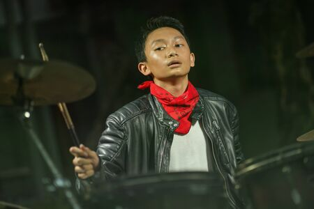 Teenager rock band musician . 13 or 14 years old cool and talented Asian American mixed ethnicity boy playing drums in leather jacket and bandana  practicing and performing song Stock Photo