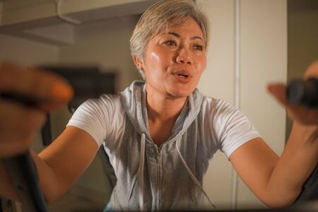 lifestyle portrait of middle aged attractive and happy Asian Indonesian woman with grey hair training exercise smiling at gym doing stationary bike workout sweaty in fitness and wellness concept