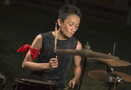 Asian American mixed teenager playing drums at home garden . cool and handsome young boy practicing on drum kit rehearsing passionate in badass rock band look enjoying the practice