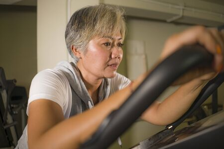 lifestyle portrait of middle aged attractive and healthy Asian Indonesian woman with grey hair training exercise at gym doing stationary bike workout sweaty in fitness and wellness concept