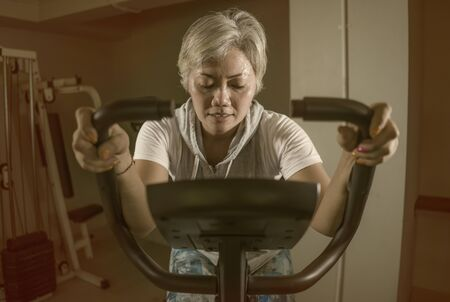 lifestyle portrait of middle aged attractive and healthy Asian Indonesian woman with grey hair training exercise at gym doing stationary bike workout sweaty in fitness and wellness concept 版權商用圖片 - 130819430