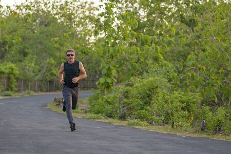 lifestyle portrait of young attractive and healthy man on his 30s or 40s running on country road doing jogging workout training happy on beautiful natural background in fitness and sport concept 免版税图像