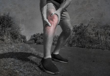 close up hands and legs of sport man injured touching his knee in pain suffering physical problem or some injury during running workout outdoors in sport accident and health care concept