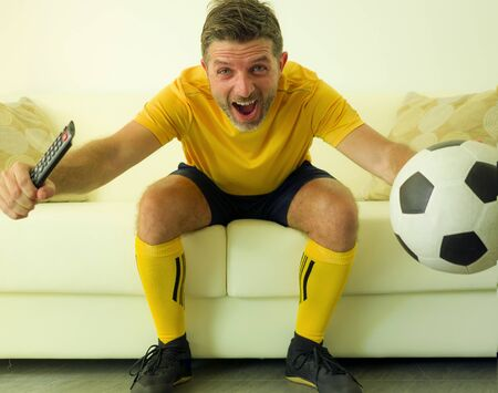 funny and crazy soccer fan man dressed in his team uniform watching football game on television celebrating scoring goal excited screaming spastic and cheering at home living room couch