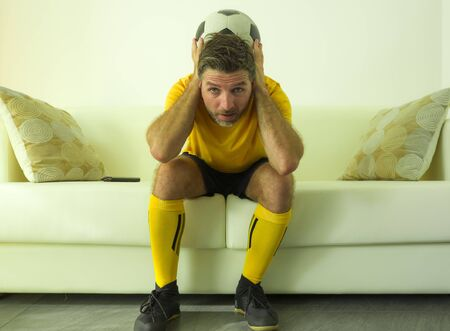 funny portrait of young stressed and excited football fan man watching soccer game on TV at home couch dressed in team player uniform feeling the stress and emotion of the competition