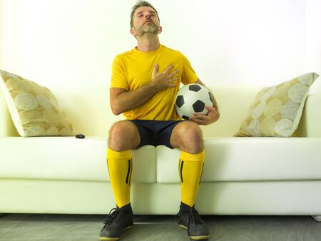 funny portrait of young man in European football team uniform watching soccer game on TV at home couch listening national anthem with hand on heart during match passionate and emotional
