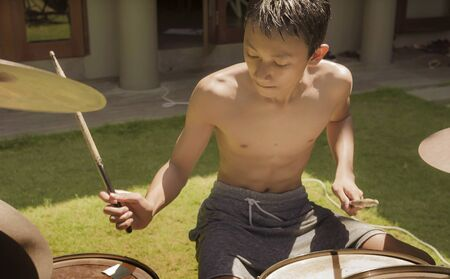 Asian American teenager playing dums. Summer portrait of handsome young boy practicing on drum kit at home garden rehearsing rock song enjoying his hobby in teen lifestyle concept