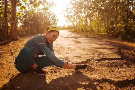 Asian jogger woman hurt while running. fitness lifestyle portrait of young attractive Chinese runner girl suffering sport injury during jogging workout on sunset road holding twisted ankle in pain Stock Photo