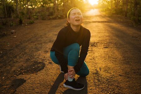 Asian jogger woman hurt while running. fitness lifestyle portrait of young attractive Chinese runner girl suffering sport injury during jogging workout on sunset road holding twisted ankle in pain