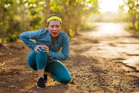 Asian jogger woman hurt while running. fitness lifestyle portrait of young attractive Chinese runner girl suffering sport injury during jogging workout on sunset road holding knee in pain