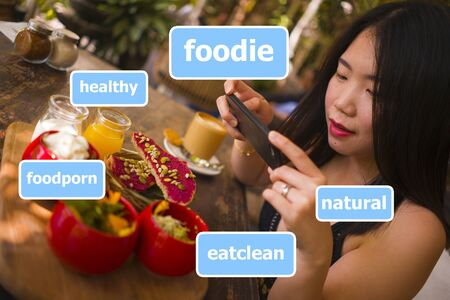 young and beautiful Asian woman takes food photography with hand phone for internet blog. Chinese girl posting online photo composed with vegetarian, healthy and organic social media hashtags 版權商用圖片