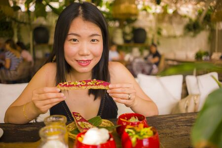 Veggie brunch . natural lifestyle portrait of young happy and beautiful Asian Chinese woman eating outdoors having organic breakfast at cool cafe in vegetarian nutrition and healthy food