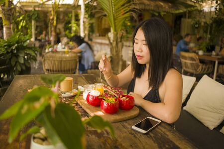 Veggie brunch . natural lifestyle portrait of young happy and beautiful Asian Korean woman eating outdoors having organic breakfast at cool cafe in vegetarian nutrition and healthy food
