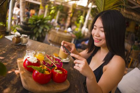 young and beautiful Asian woman takes photography of food on table with phone for internet blog. Chinese girl posting online photo for vegetarian, healthy and organic social media