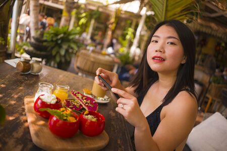 young and beautiful Asian woman takes photography of food on table with phone for internet blog. Korean girl posting online photo for vegetarian, healthy and organic social media 版權商用圖片