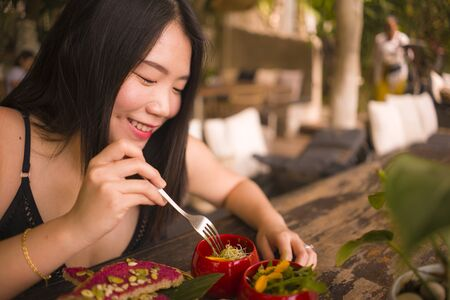 Veggie brunch . natural lifestyle portrait of young happy and beautiful Asian Japanese woman eating outdoors having organic breakfast at cool cafe in vegetarian nutrition and healthy food